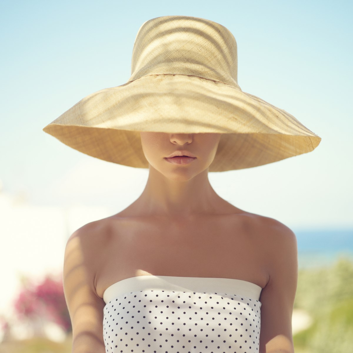 Beautiful young lady in straw hat in the sunlight